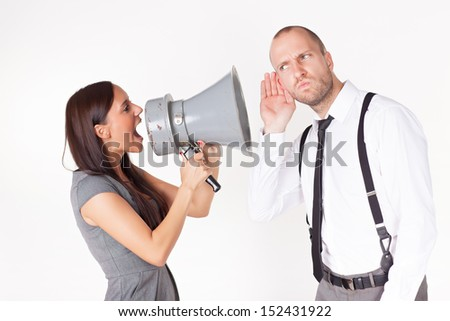 Businesswoman shouting at a businessman with megaphone  - stock photo