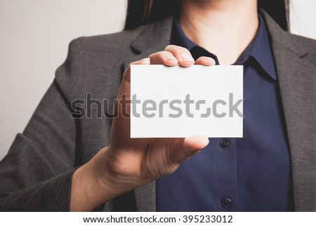 Businesswoman showing and handing a blank business card. - stock photo
