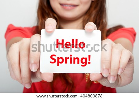 Businesswoman showing card with hello spring message, - stock photo