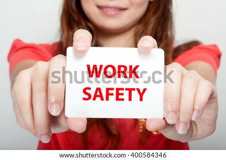 Businesswoman showing card with work safety message, - stock photo