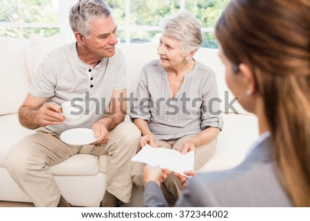 Businesswoman showing documents to senior couple at home - stock photo
