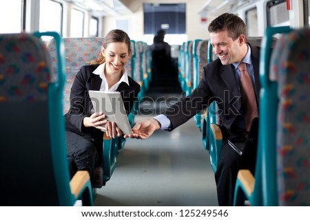 Businesswoman showing her colleague something on her tablet computer - stock photo
