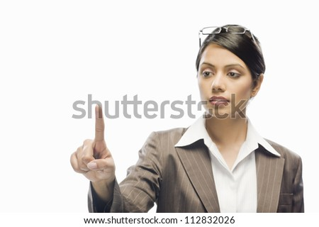 Businesswoman showing her index finger against a white background - stock photo
