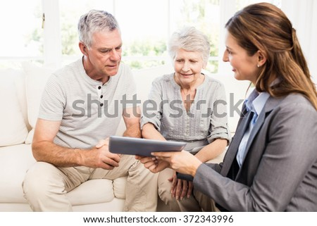 Businesswoman showing tablet to senior couple at home - stock photo