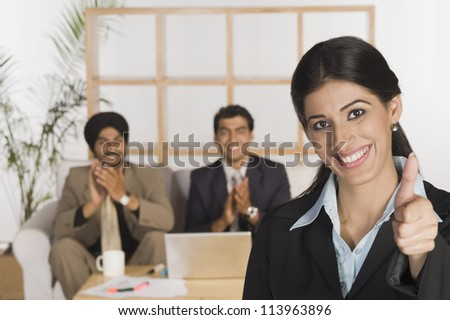 Businesswoman showing thumbs up sign - stock photo