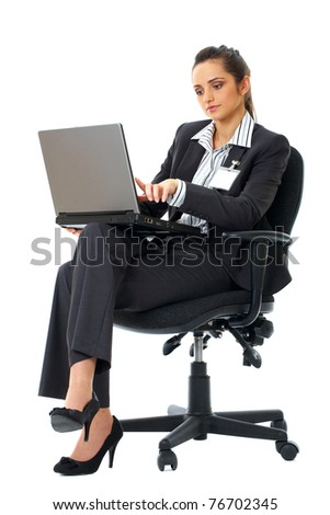 businesswoman sits on chair and work on her laptop, isolated on white - stock photo