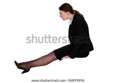 businesswoman sitting and watching her shoes - stock photo