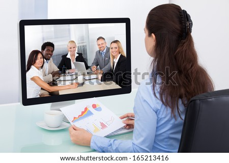 Businesswoman Sitting At A Desk Watching An Online Presentation On The Computer - stock photo