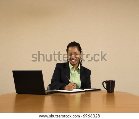 Businesswoman sitting at conference table with laptop computer and coffee cup smiling and writing in book. - stock photo