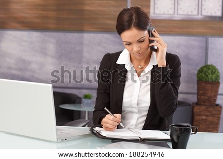 Businesswoman sitting at desk in office, talking on mobilephone, writing notes to organizer, having laptop. - stock photo