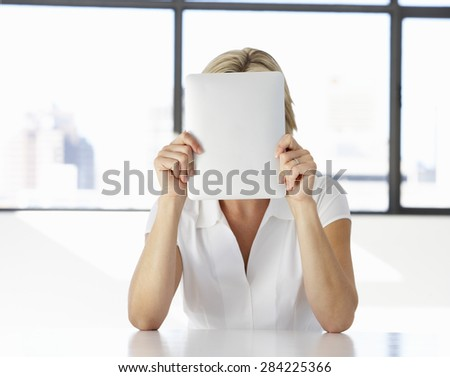Businesswoman Sitting At Desk In Office With Face Hidden Behind Digital Tablet - stock photo
