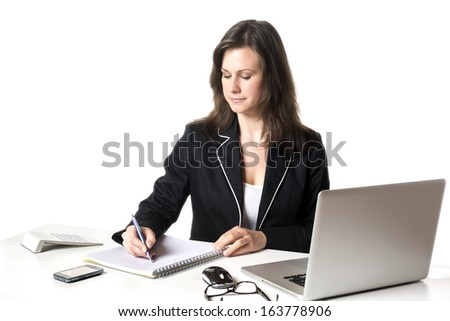 Businesswoman sitting at desk in office, writing something on a pad, isolated on white background - stock photo