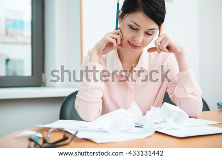 Businesswoman sitting at desk in the office in thoughts.