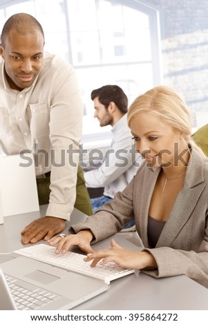Businesswoman sitting at desk, typing on keyboard, male colleague assisting. - stock photo