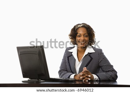 Businesswoman sitting at desk with computer smiling.