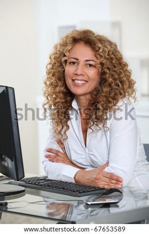Businesswoman sitting at her desk in office - stock photo