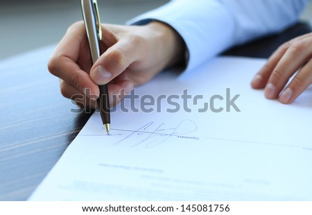 Businesswoman sitting at office desk signing a contract with shallow focus on signature. - stock photo