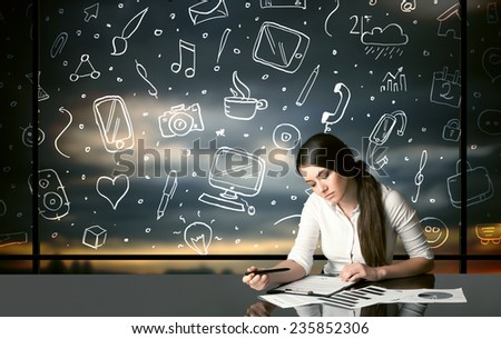 Businesswoman sitting at table with hand drawn social media icons and symbols  - stock photo