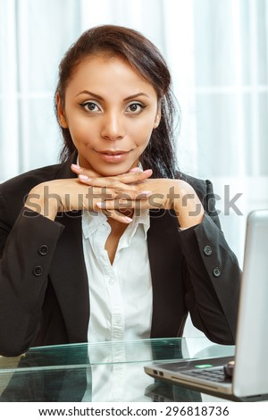 Businesswoman sitting at the desk - stock photo