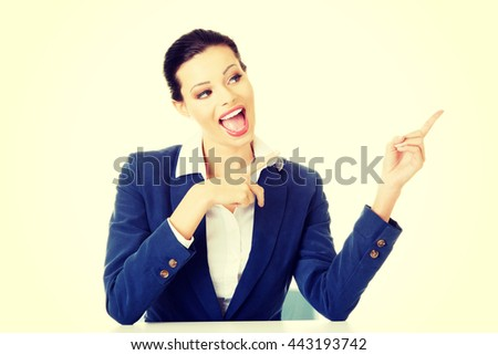 Businesswoman sitting at the desk and pointing on empty copy spa - stock photo
