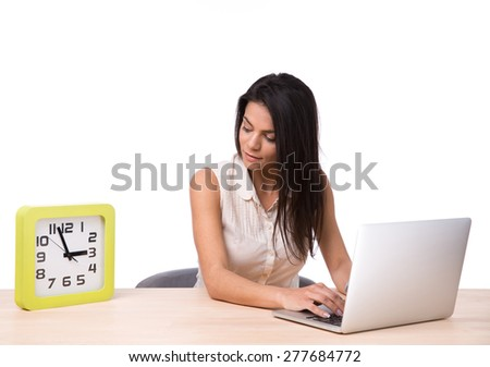 Businesswoman sitting at the table with laptop and looking on clock over white background - stock photo