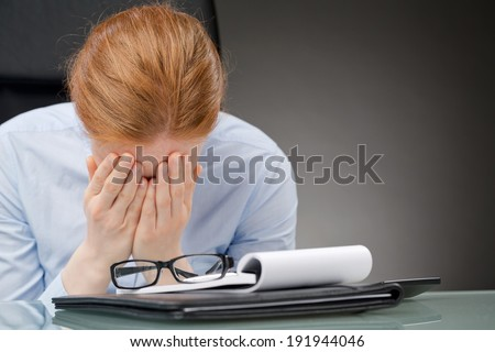 Businesswoman sitting behind a desk with face buried in her hands, copy space on the right. - stock photo