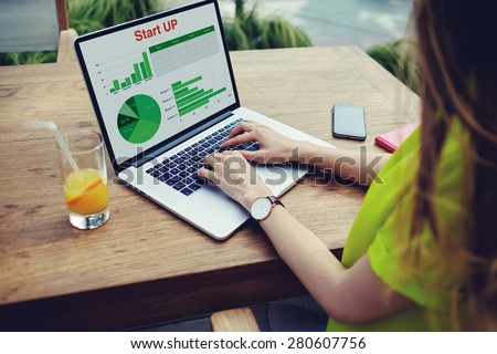 Businesswoman sitting front laptop computer with financial information as graphics and charts on screen, young female entrepreneur work with statistics data and analyzing performance on her notebook  - stock photo