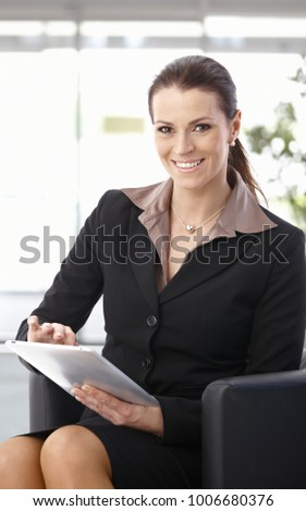 Businesswoman sitting in armchair at office using tablet computer, looking at camera, smiling.