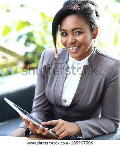 Businesswoman Sitting In Modern Office Using Digital Tablet - stock photo