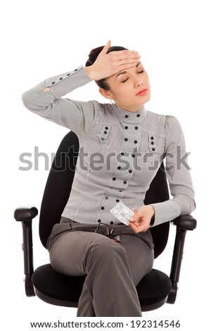 businesswoman sitting in the office chair with headache holding pills over white background - stock photo