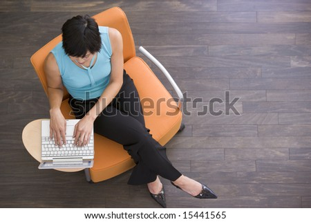 Businesswoman sitting indoors with laptop - stock photo