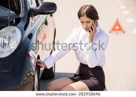 Businesswoman sitting near broken car and calling for help on phone. - stock photo