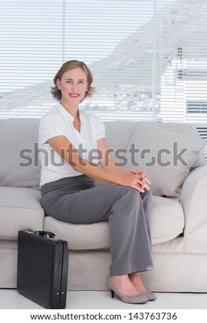 Businesswoman sitting on couch waiting in a waiting room