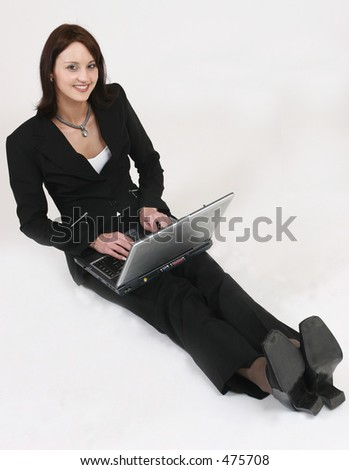 Businesswoman sitting on ground working on her computer