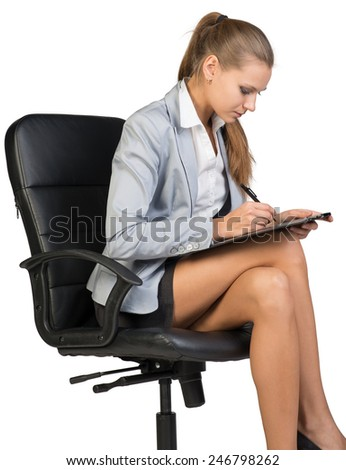 Businesswoman sitting on office chair with clipboard and writing. Isolated over white background