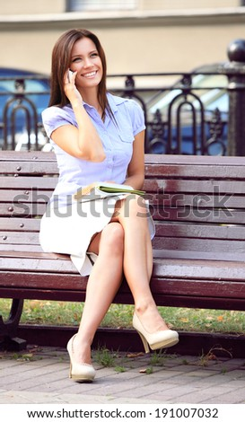 Businesswoman sitting on park bench  - stock photo