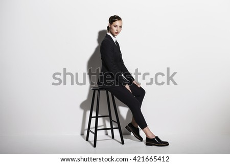 Businesswoman sitting on stool, portrait