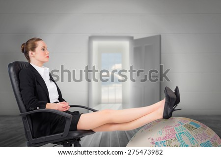 Businesswoman sitting on swivel chair with feet up against open door leading to bright window - stock photo