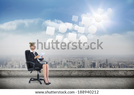 Businesswoman sitting on swivel chair with tablet against balcony overlooking city - stock photo