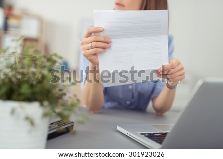 Businesswoman sitting thinking with a folded document in her hands looking off to the side, close up of the sheet of paper and her hand - stock photo