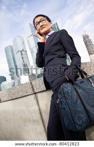 Businesswoman, skyscraper background - stock photo