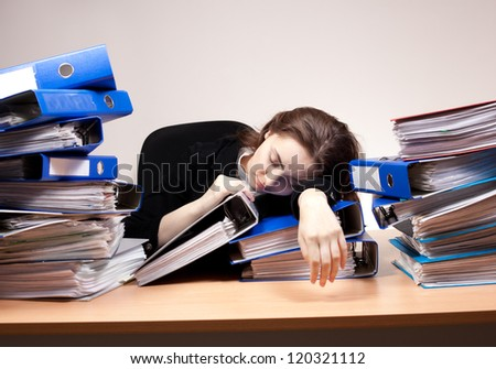 Businesswoman sleeping at office with stack of folders - stock photo