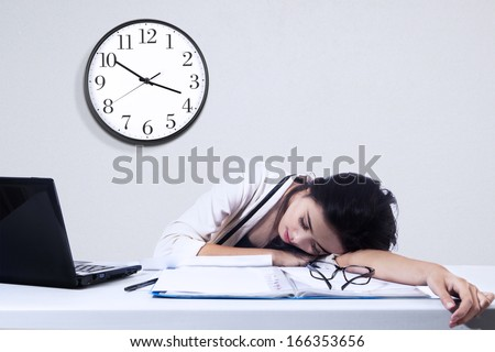 Businesswoman sleeping with laptop computer on the desk in office - stock photo