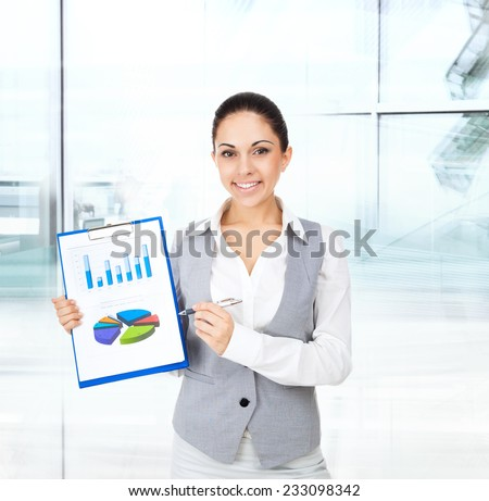 Businesswoman smile hold clipboard paper report document with finance chart, diagram, young attractive business woman in modern office - stock photo