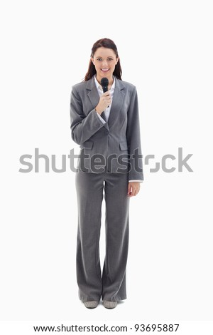 Businesswoman smiling and holding a microphone against white background
