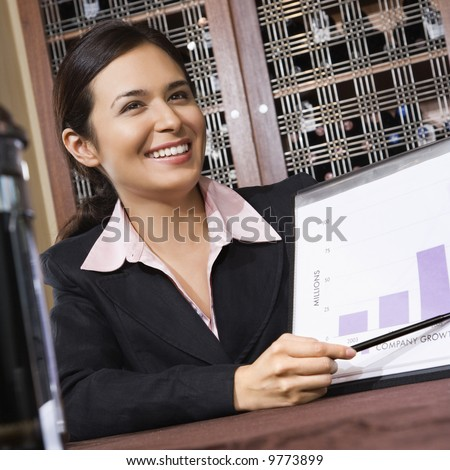 Businesswoman smiling and pointing to bar graph.