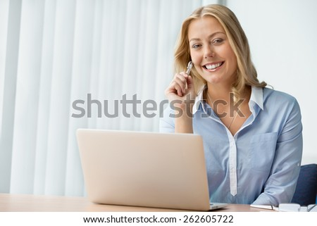 Businesswoman smiling and sitting in offfice