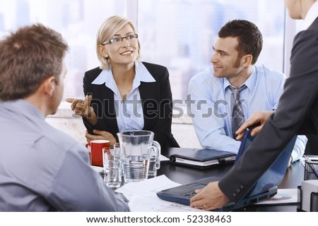 Businesswoman smiling at assistant opening laptop, colleagues listening. - stock photo