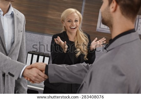 Businesswoman smiling happy, clapping hands over successful business agreement sealed with handshake. - stock photo