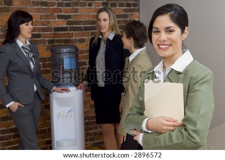 businesswoman smiling in front of team talking at water cooler. - stock photo